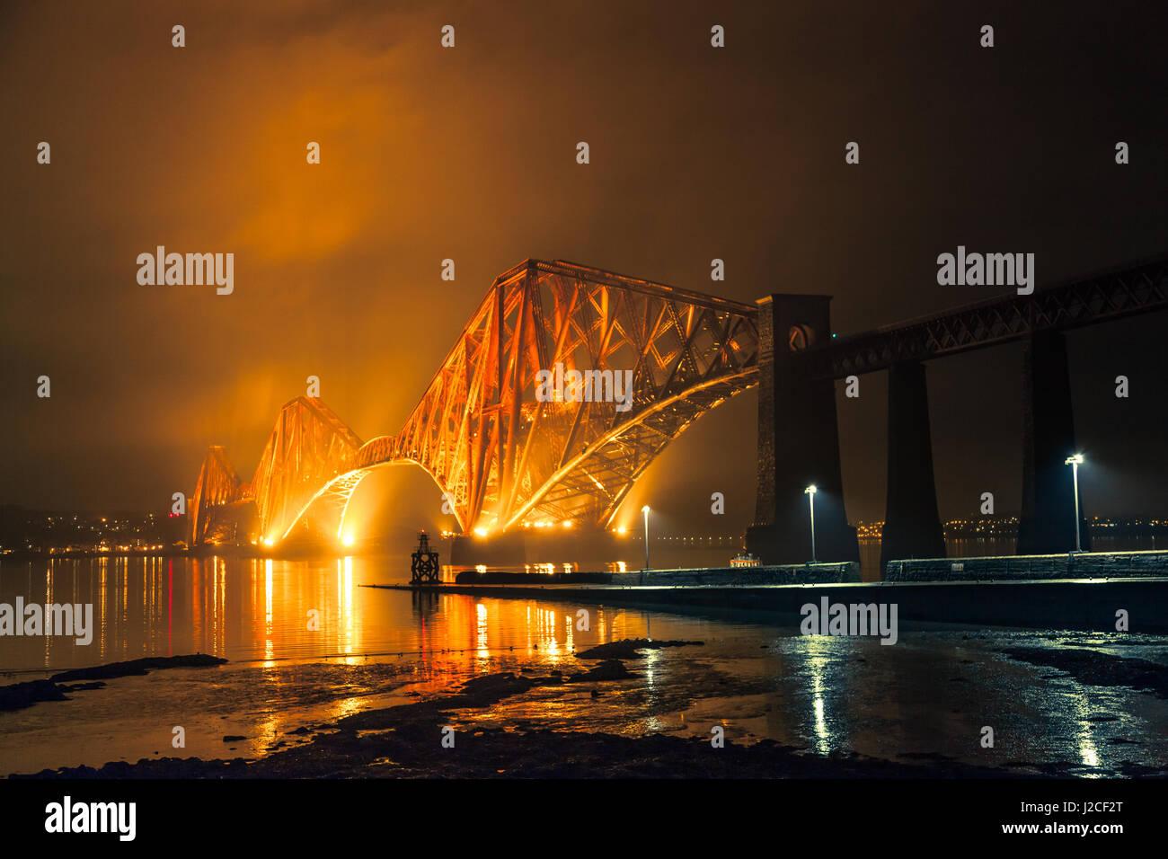 Die Forth Rail Bridge beleuchtet nachts. Goldenen Licht den Himmel oben. South Queensferry, Edinburgh, Schottland Stockbild