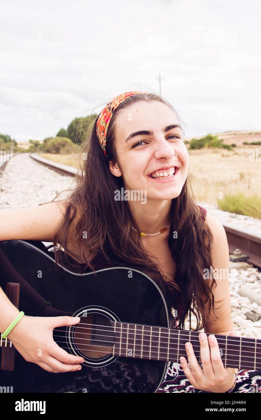 Brünette Teen Frau mit ihrer Gitarre Stockbild