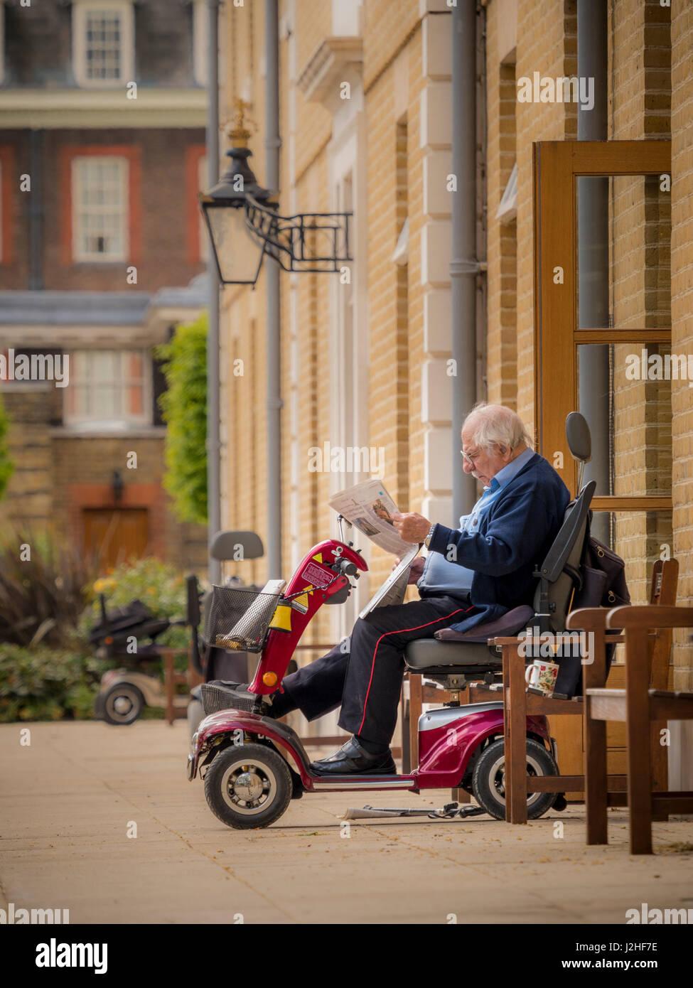 Chelsea Pensionär am Royal Hospital Chelsea saß auf Elektromobil außerhalb Wohnung lesen Zeitung, Stockbild