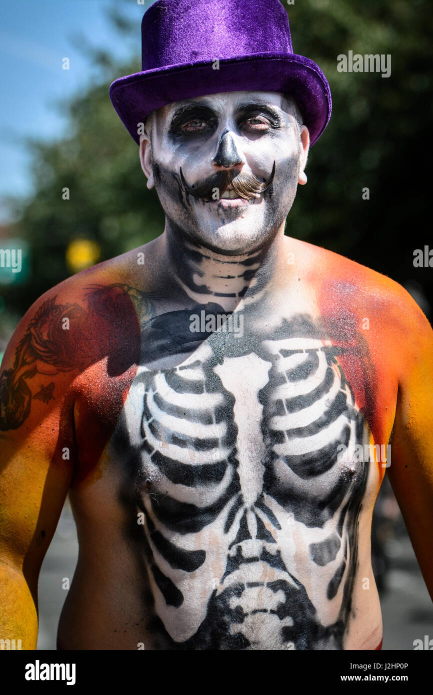 Seattle, Washington. Mann mit Skelett Körper Farbe und lila Hut bei ...