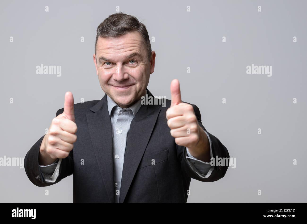 Grinsenden Mann im dunklen Anzug-Jacke mit zwei Daumen hoch über dem grauen Hintergrund. Textfreiraum umfasst. Stockbild