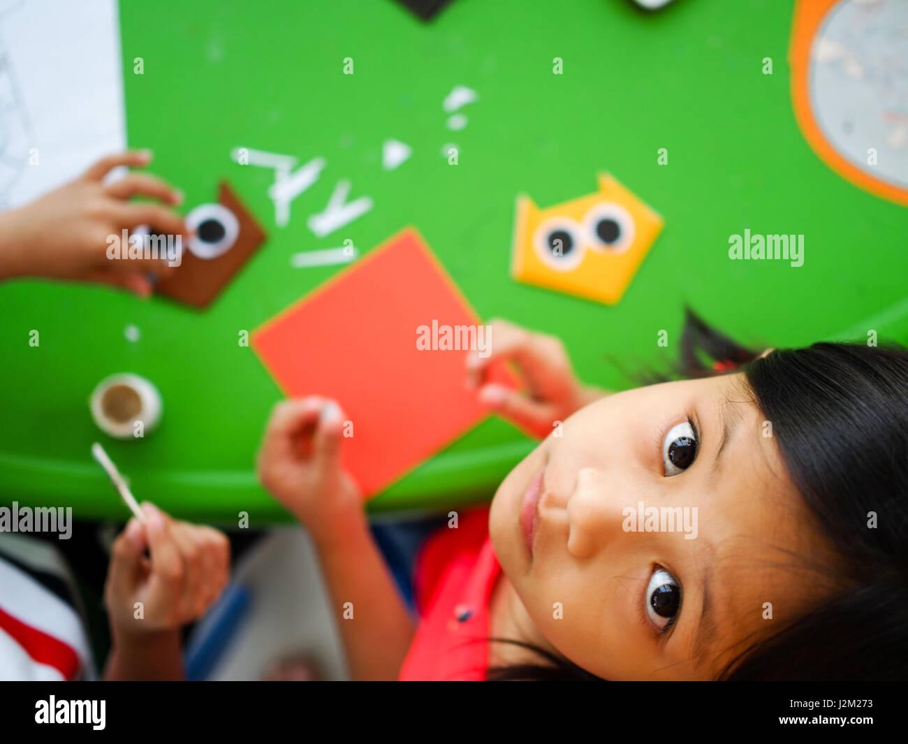Asiatische Kind spielt mit Origami-Papier Stockbild