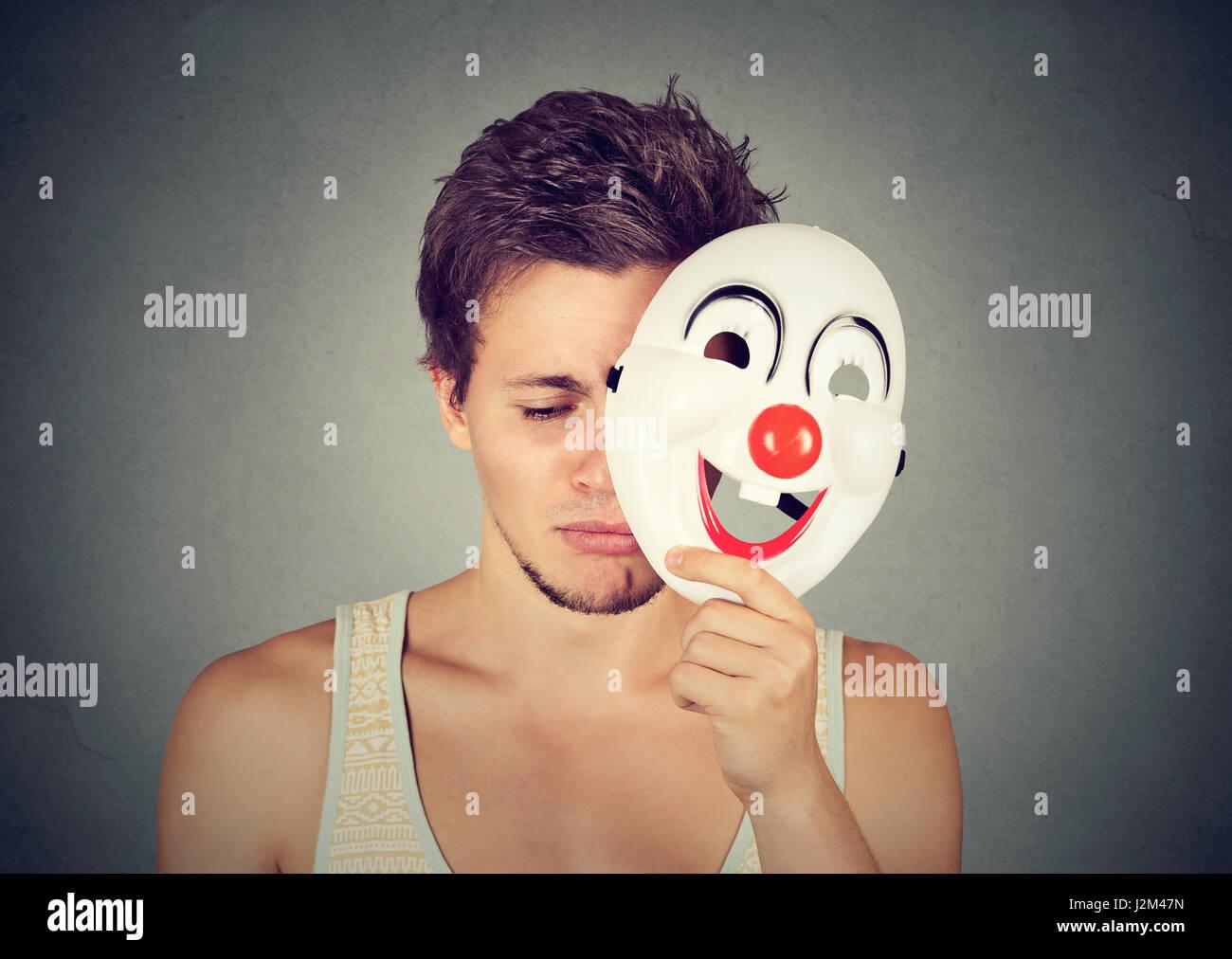 Trauriger Jüngling Clownsmaske isoliert auf graue Wand Hintergrund abheben. Menschliche Gefühle Stockbild