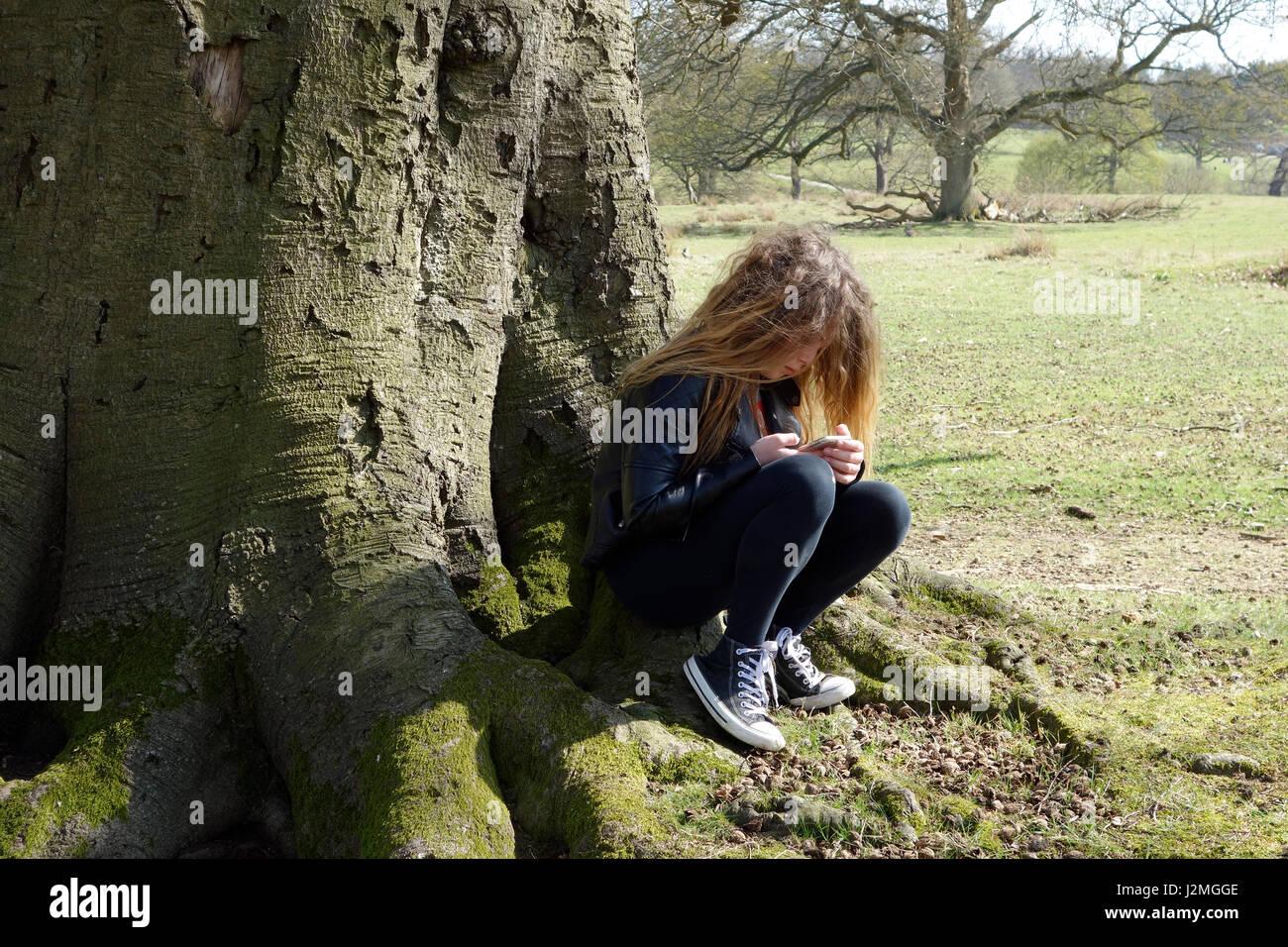 11 Jahre altes Mädchen sitzen unter Baum Stockbild