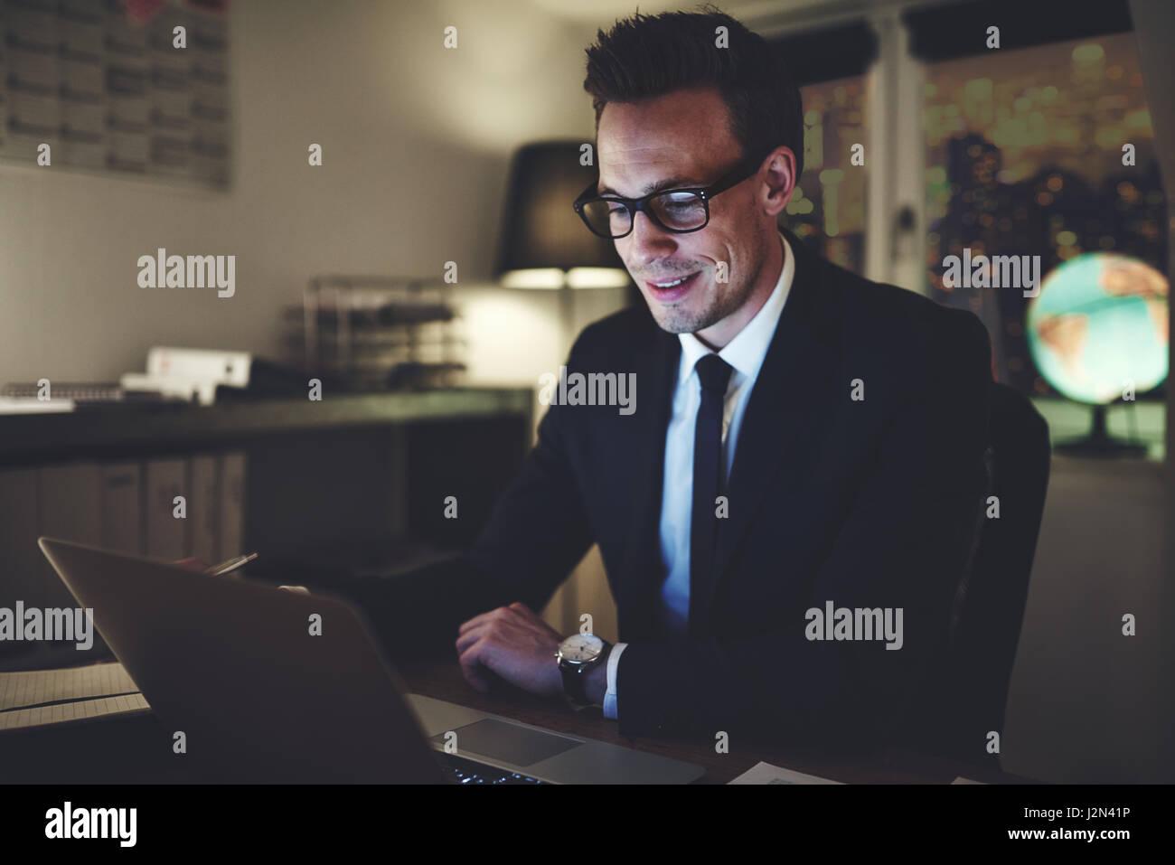 Lächelnd Geschäftsmanns, der auf dem Laptop in der Nacht im Büro suchen konzentriert Stockbild