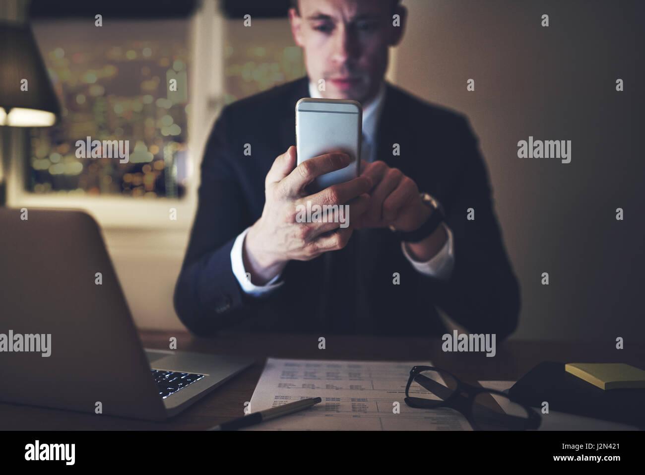 Eine nachdenkliche intelligente Manager im Büro zu sitzen und sein Smartphone surfen. Stockfoto