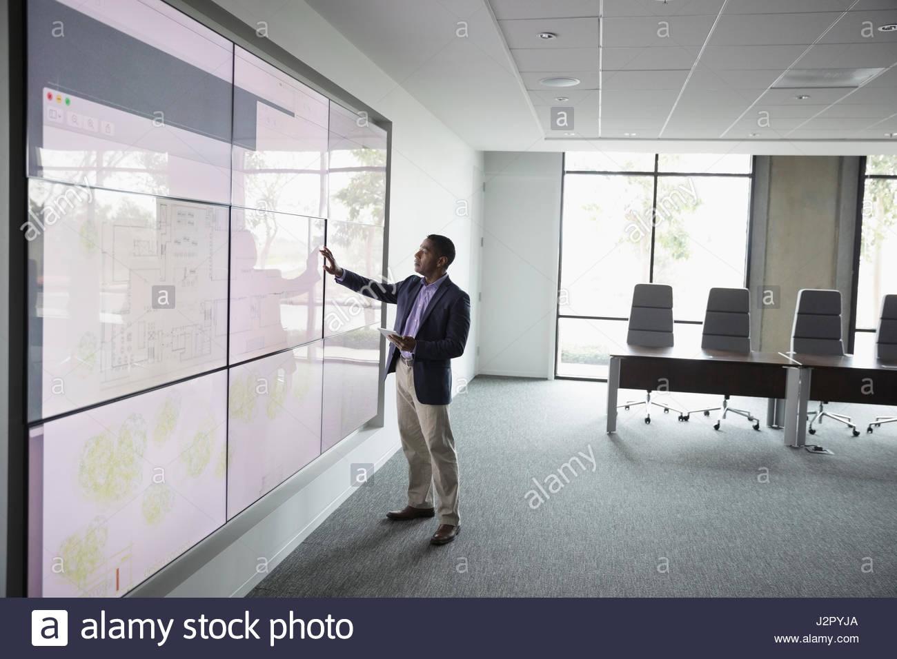 Afrikanische amerikanische männliche Architekten arbeiten bei großen Touchscreen im Konferenzraum Stockbild