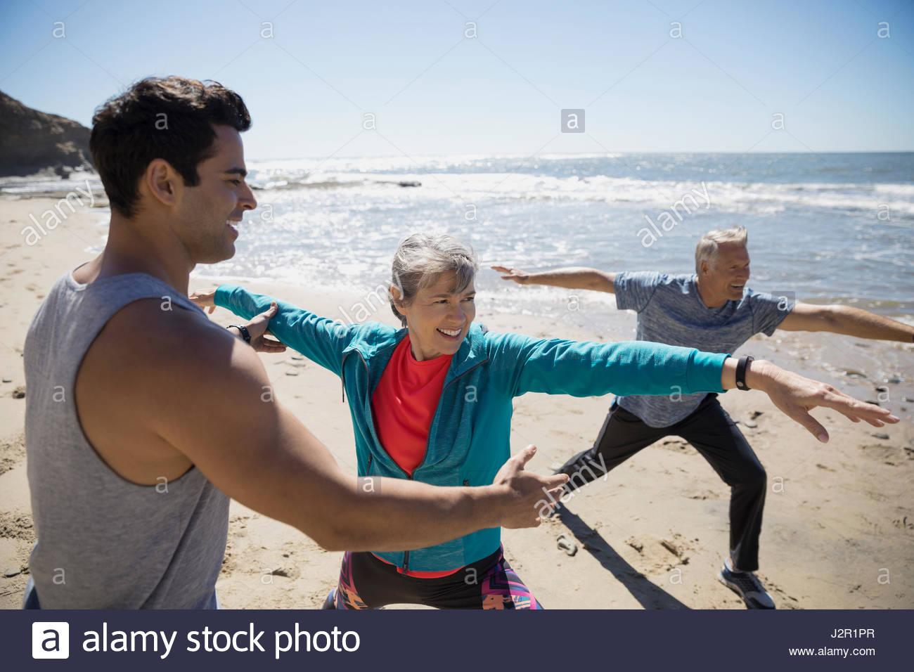 CrossFit Trainer helfen älteres paar trainieren, üben Yoga Warrior 2-Pose am Sonnenstrand Stockfoto