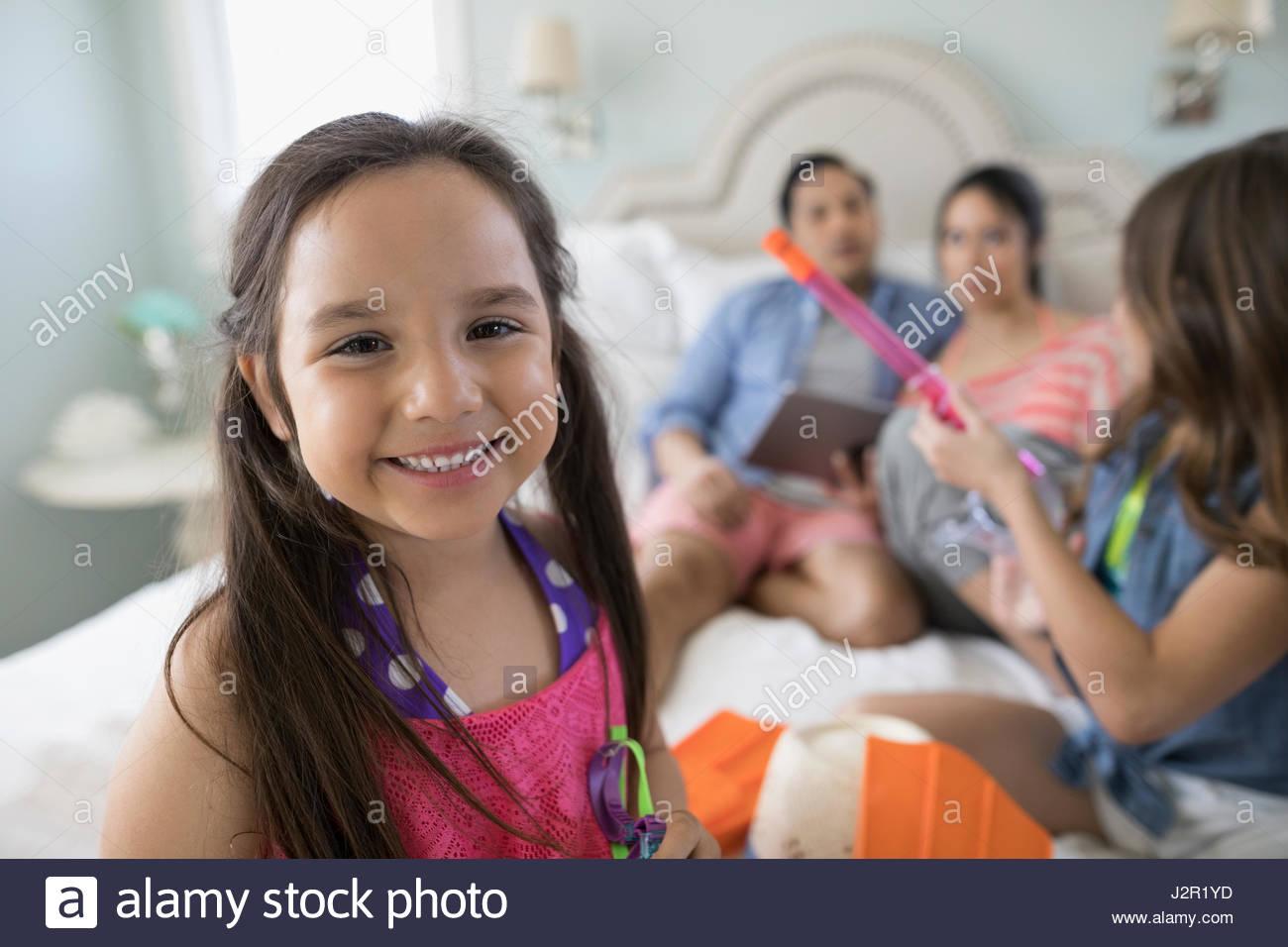 Porträt, lächelndes Mädchen auf dem Bett mit Familie Stockbild