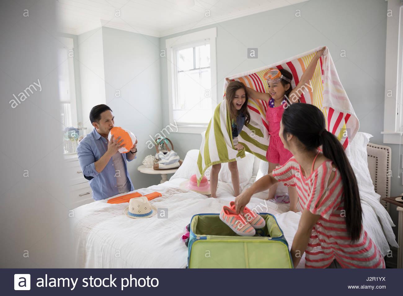 Familie, Verpackung für Urlaub, spielen auf Bett Stockbild