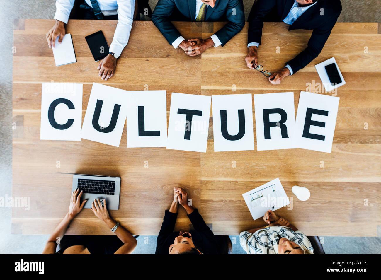 Draufsicht von Geschäftsleuten mit Wort Kultur auf Tisch. Geschäftsleute, ein Treffen und diskutieren Stockbild