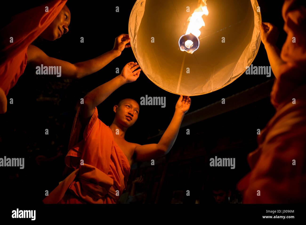 CHIANG MAI, THAILAND - 7. November 2014: Junge buddhistische Mönche in orangefarbenen Gewändern starten Himmelslaternen Stockfoto