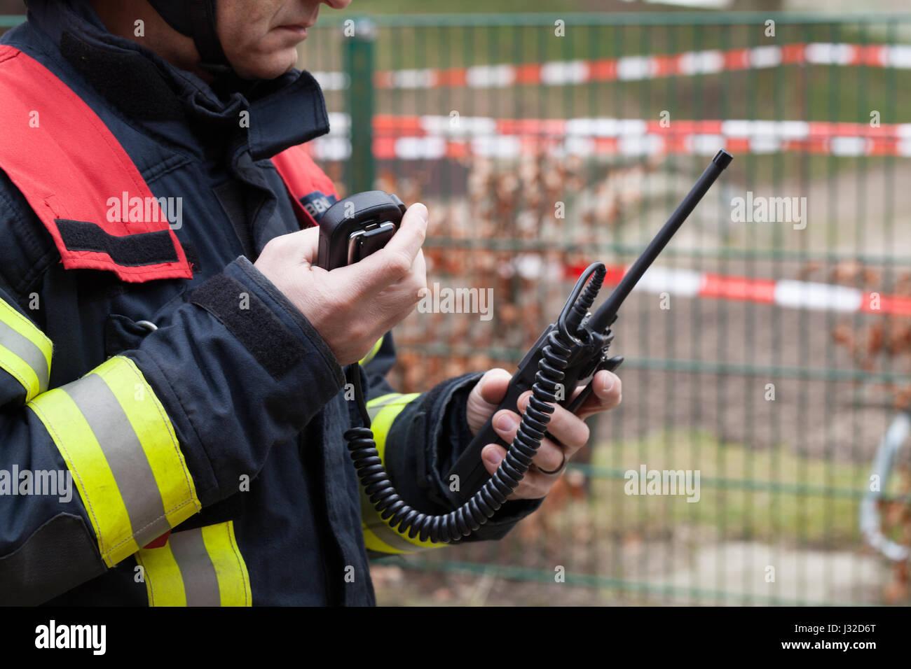 Deutsche Feuerwehr-Führer verwendet ein Walkie-Talkie in Aktion Stockbild