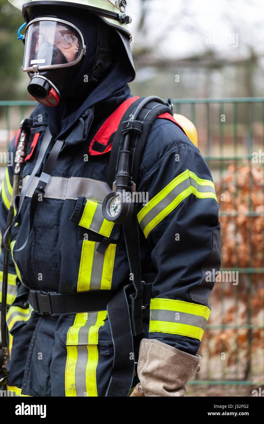 Deutscher Feuerwehrmann im Freien in Aktion und mit Sauerstoff-Flasche und Maske Stockbild