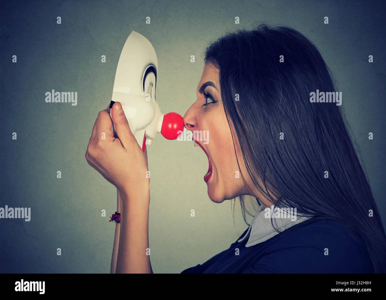Böse Frau schreiend auf happy Clownsmaske Stockfoto