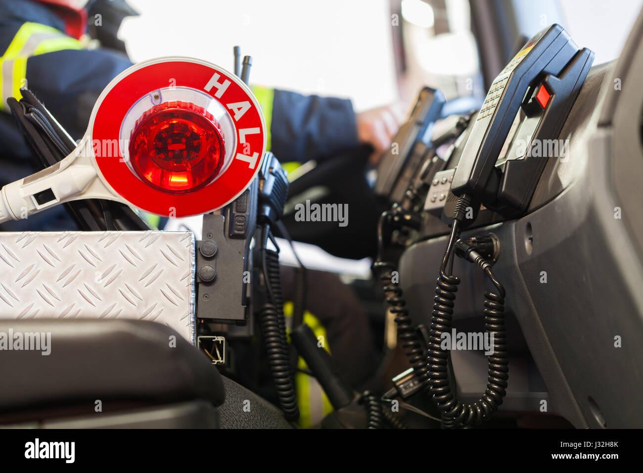 Feuerwehrmann fährt ein Einsatzfahrzeug mit Kommunikation Innenansicht und Kelle Stockbild