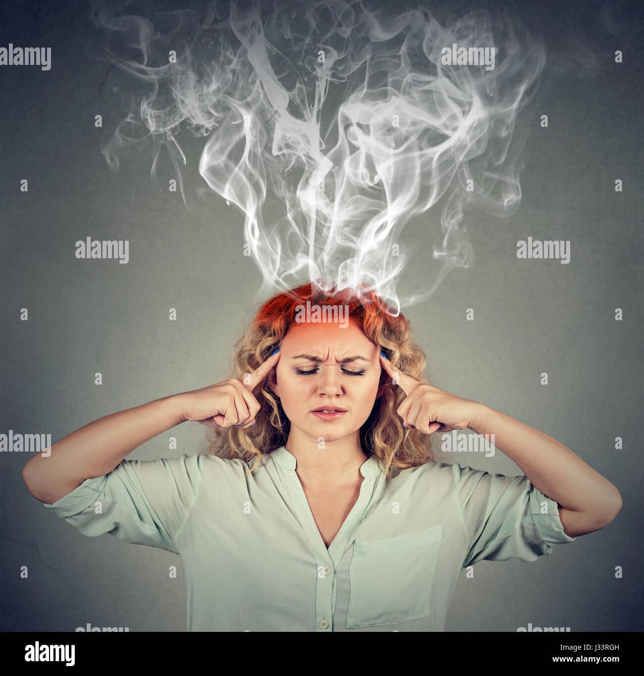Frau denkt sehr intensiv mit Kopfschmerzen auf graue Wand Hintergrund isoliert Stockbild