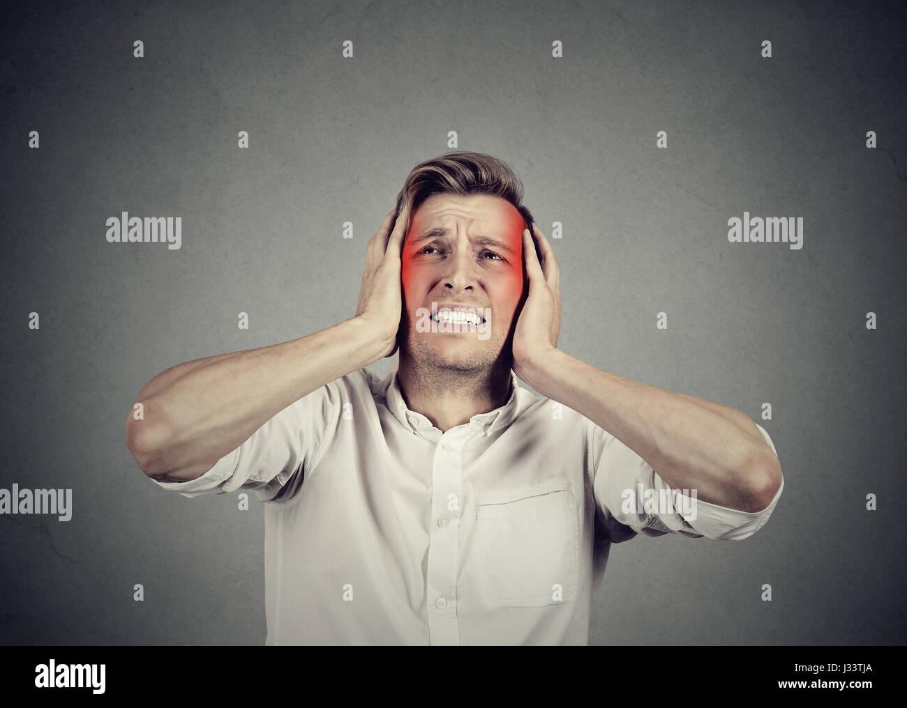 Mann mit Kopfschmerzen auf graue Wand Hintergrund isoliert Stockbild