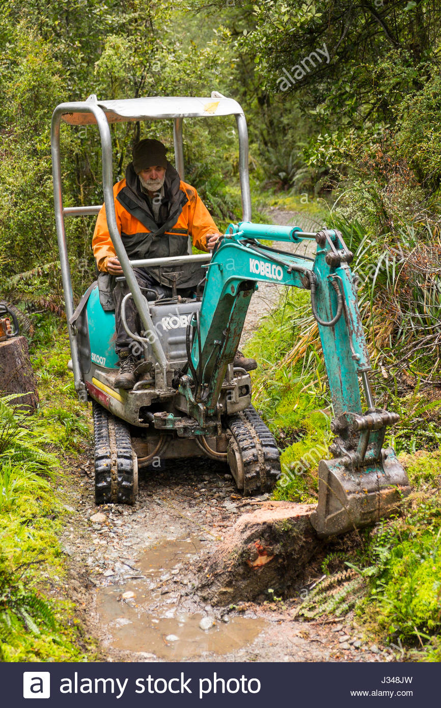 Mann Mit Einer Kobelco SK007 Mini Bagger Baumstumpf Entfernen Von Milford Track Fjordland National Park Southland Sudinsel Neuseeland