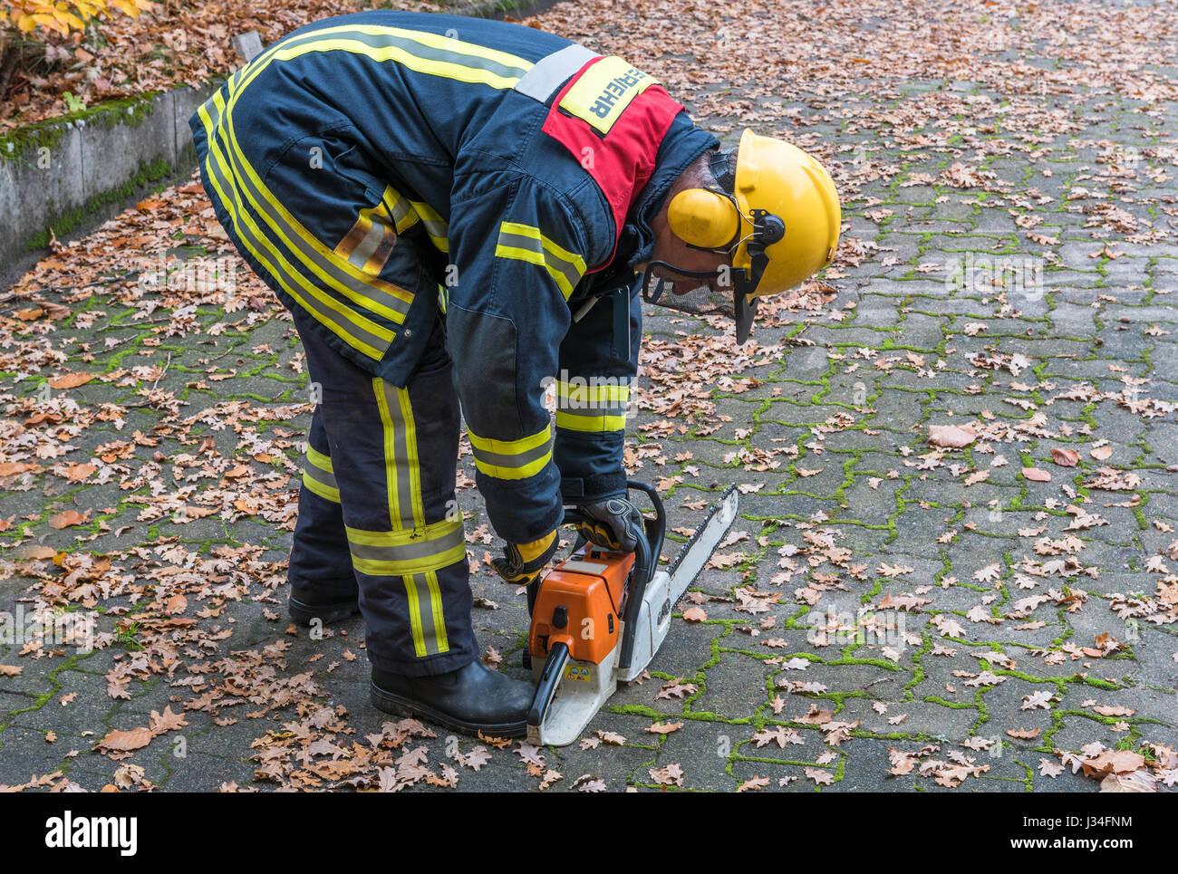 Deutscher Feuerwehrmann im Einsatz im Freien mit Kettensäge Stockbild