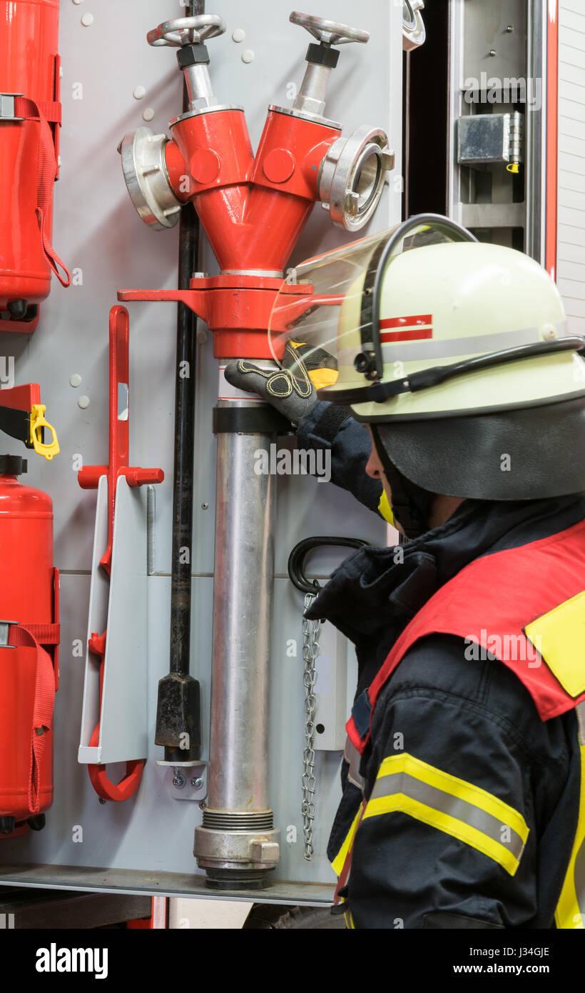 Feuerwehrmann arbeitet an dem Feuerwehrauto Stockbild