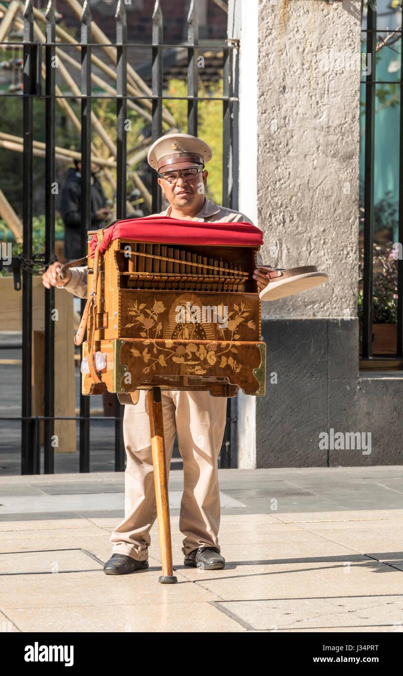 Mexiko-Stadt, Mexiko-22 April 2017: traditionelle Drehorgelspieler Kurbeln seiner Orgel, ein Hut für Spenden Stockbild