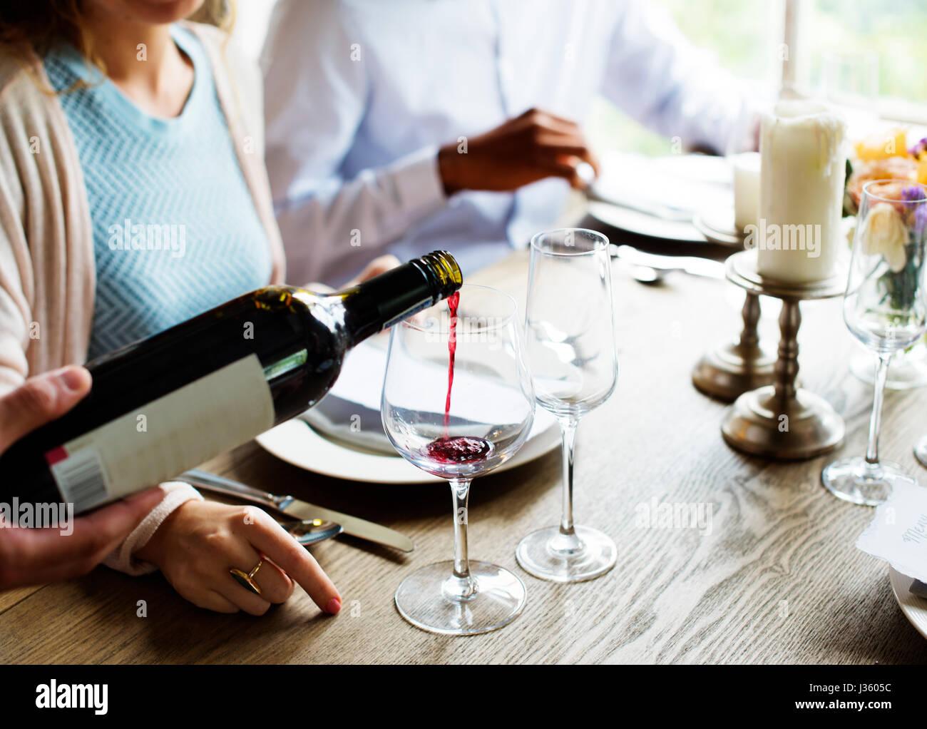 Poring Kellner servieren Rotwein zu Kunden in einem Restaurant Stockbild