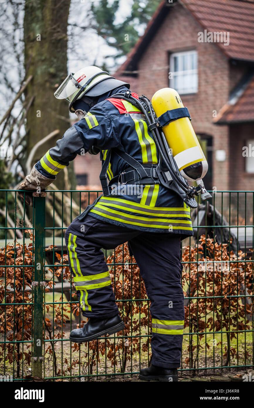 Feuerwehrmann im Einsatz im Freien mit Sauerstoffmaske und Sauerstoffflasche Stockbild