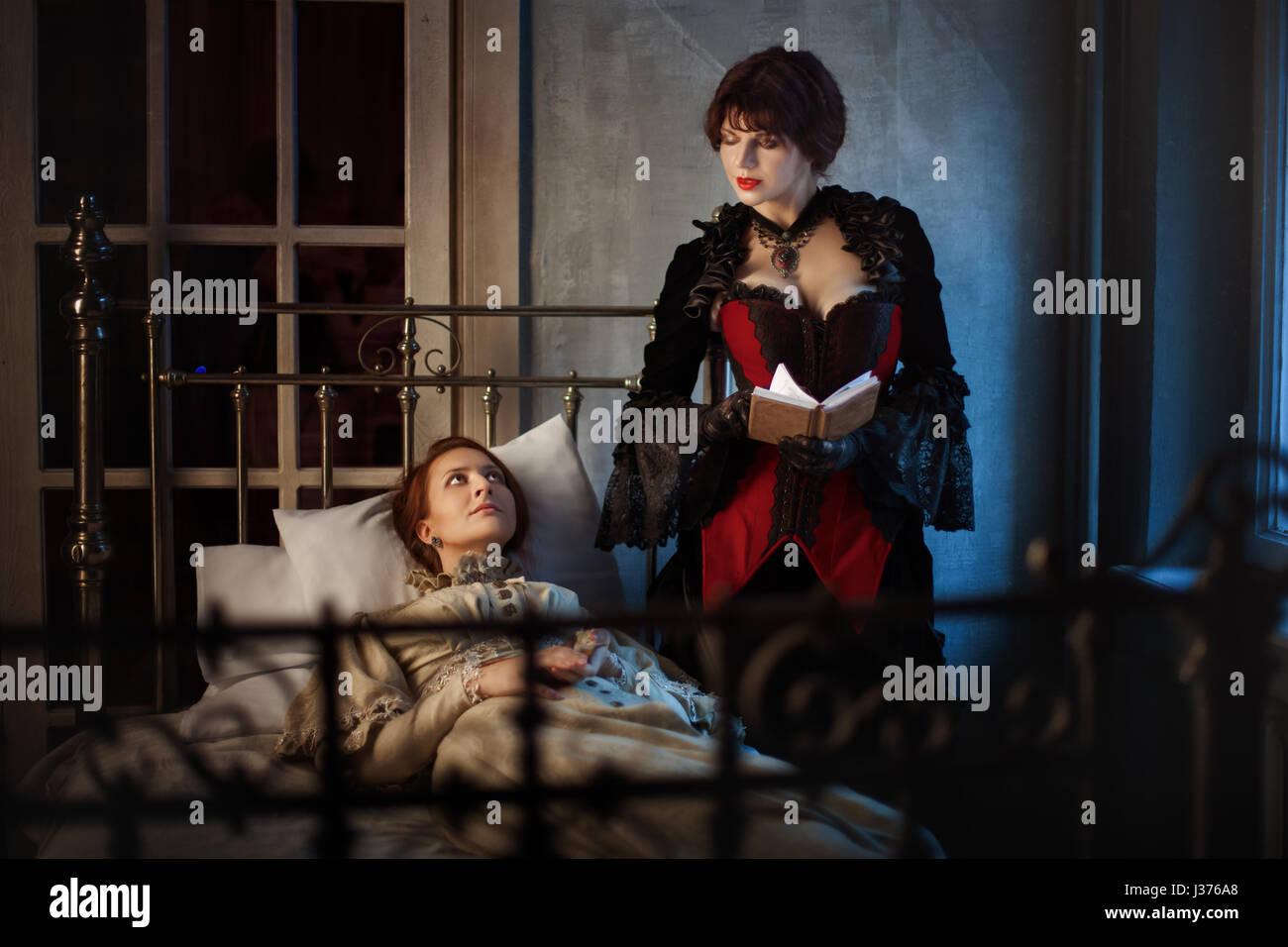 Kranke Frau liegend auf einem Bett neben einer anderen Frau ein Buch lesen, im Retro-Stil Gotik. Stockbild