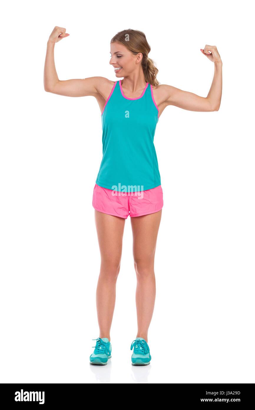 Schöne junge Frau in rosa Shorts, grüne Tank-Top und Turnschuhe stehend mit Armen ausgestreckte und biegen Stockbild
