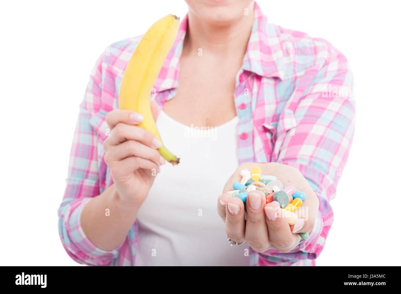 Frau mit Banane und Tablet Pillen als alternative Nährstoffe Konzept auf weißem Hintergrund Stockbild