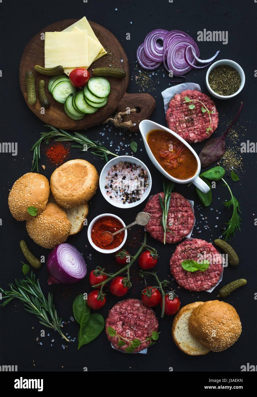 Zutaten für das Kochen Burger. Rohen Boden Rindfleisch Fleisch Schnitzel, Brötchen, rote Zwiebel, Cherry Stockbild