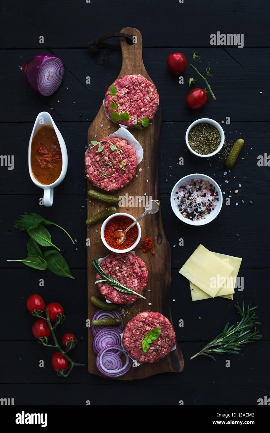 Zutaten für das Kochen Burger. Rohen Boden Rindfleisch Fleisch Schnitzel auf Schneidbrett aus Holz, rote Zwiebel, Stockbild