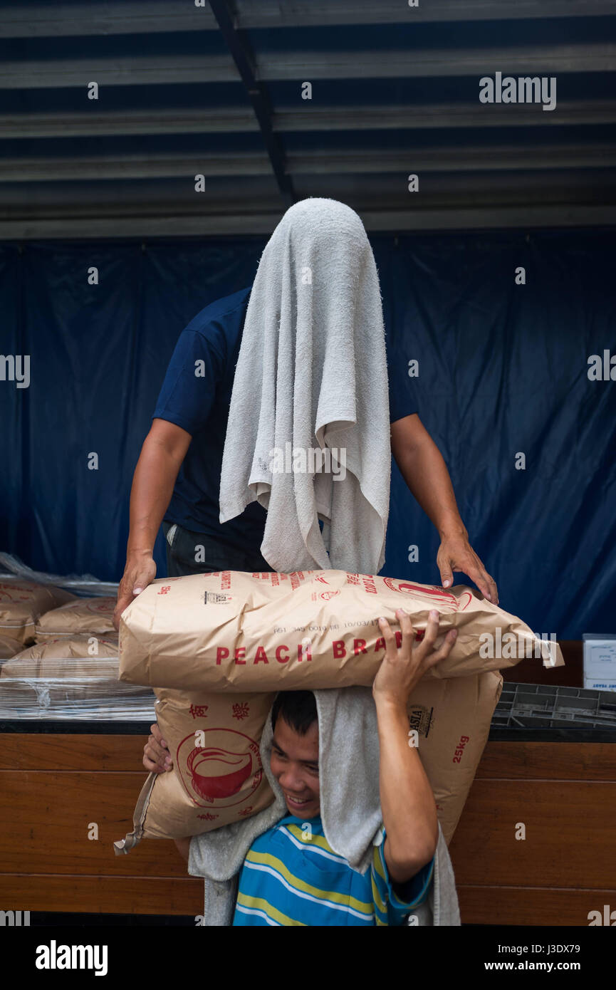 Singapur, Republik Singapur, Asien, Arbeiter entladen Mehlsäcke Stockbild