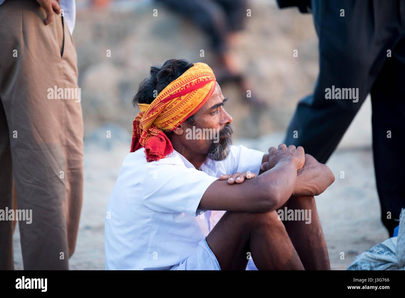 Männer schauen sitzt auf dem Boden inmitten einer Menschenmenge in Kanyakumari, Indien Stockbild