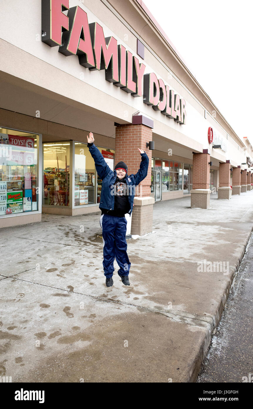 Junge springt vor dem Family Dollar Geschäft. St Paul Minnesota MN USA Stockbild