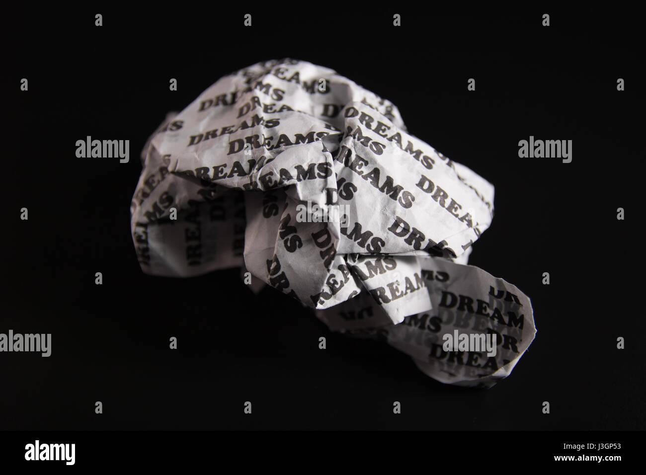 """Ein zerknittertes Papier mit den Worten """"träumt"""" schriftliche überall auf einem schwarzen Hintergrund. Stockbild"""