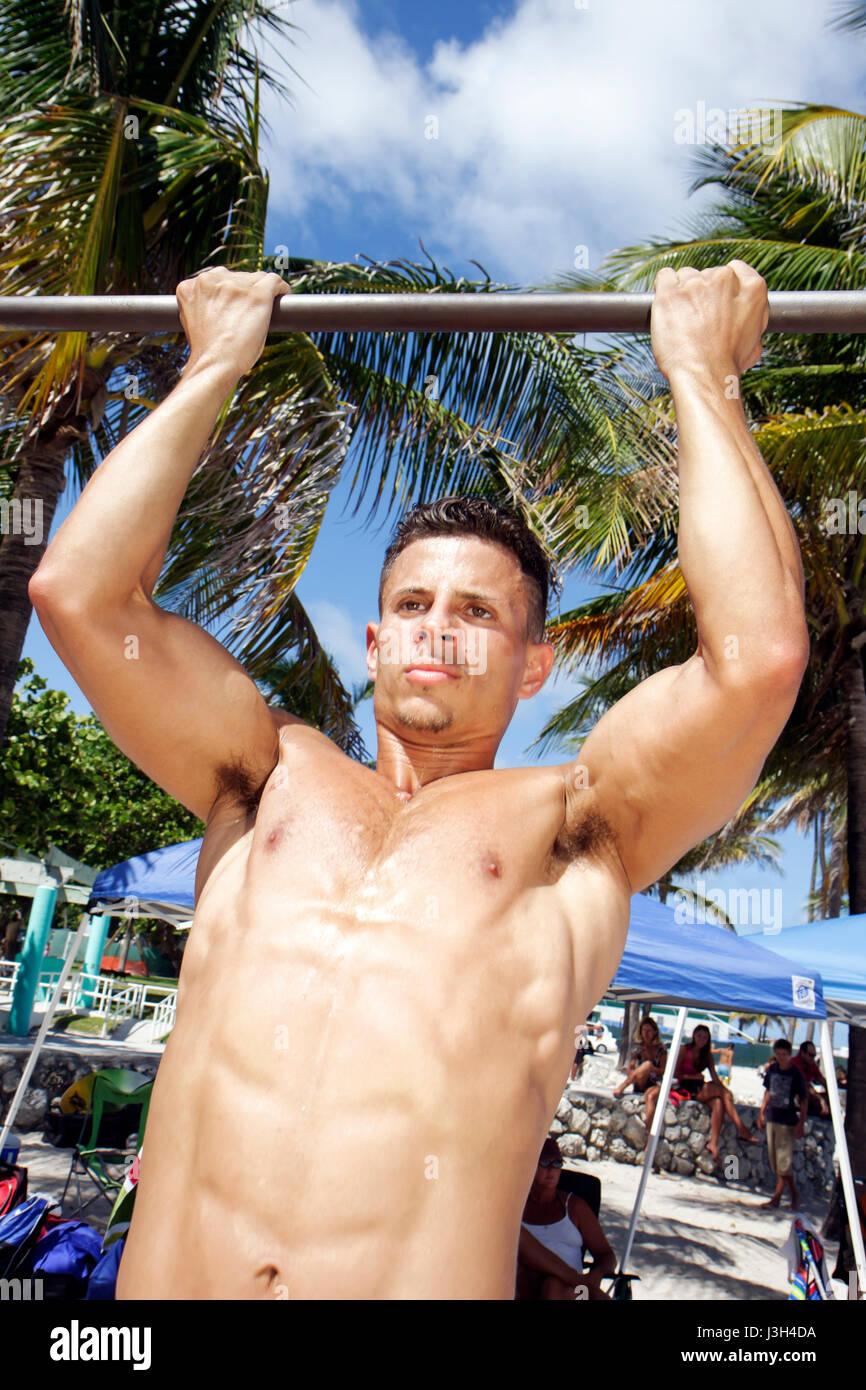 Miami Beach Florida Lummus Park Hispanic Mann Junge Pull-up Fitness fit muskulös Übung Gesundheit Muskeln Tan Sonne Stockfoto