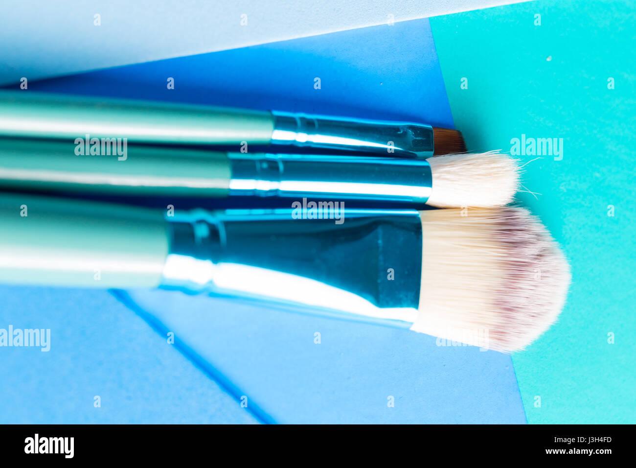 Ihr Leben in Shades of Blue: Stillleben mit einem Make-up-Pinsel platziert auf einem Multi-Ton-Schattierungen von blau. Stockfoto