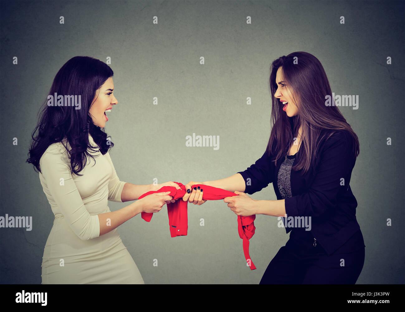 zwei gierige Frauen kämpfen um roten Tank-Top an grauen Wand Hintergrund Stockbild