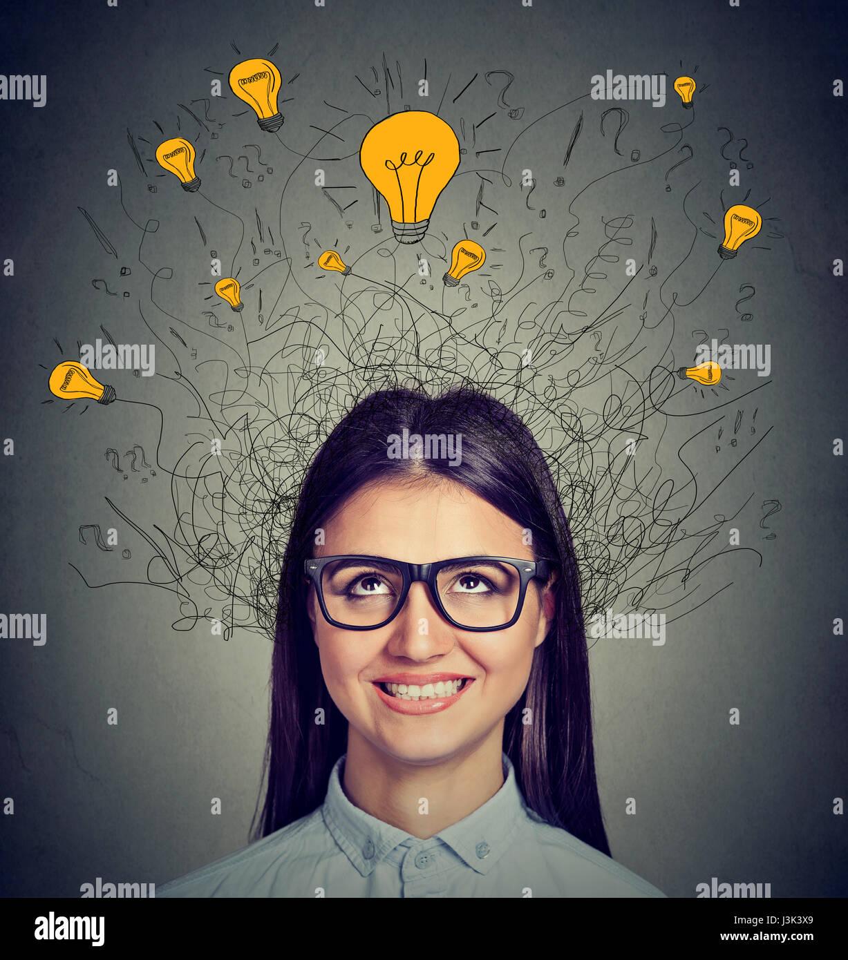 Junge Frau mit vielen Ideen, die Glühbirnen über Kopf nach oben isoliert auf graue Wand Hintergrund. Eureka Stockbild
