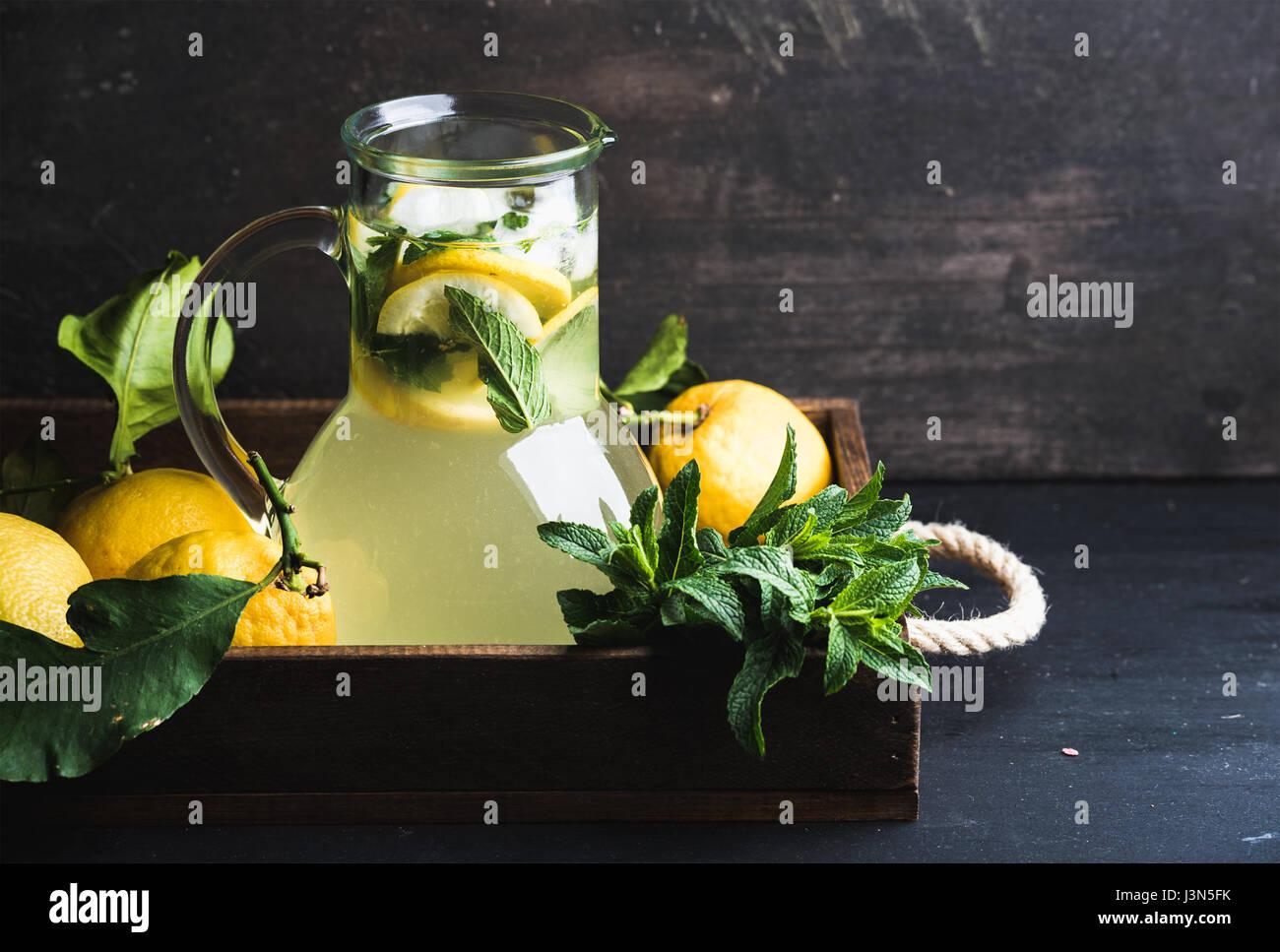 Hausgemachte Minzlimonade, serviert mit frischen Zitronen und Eis über hölzerne Hintergrund, Draufsicht, Stockbild