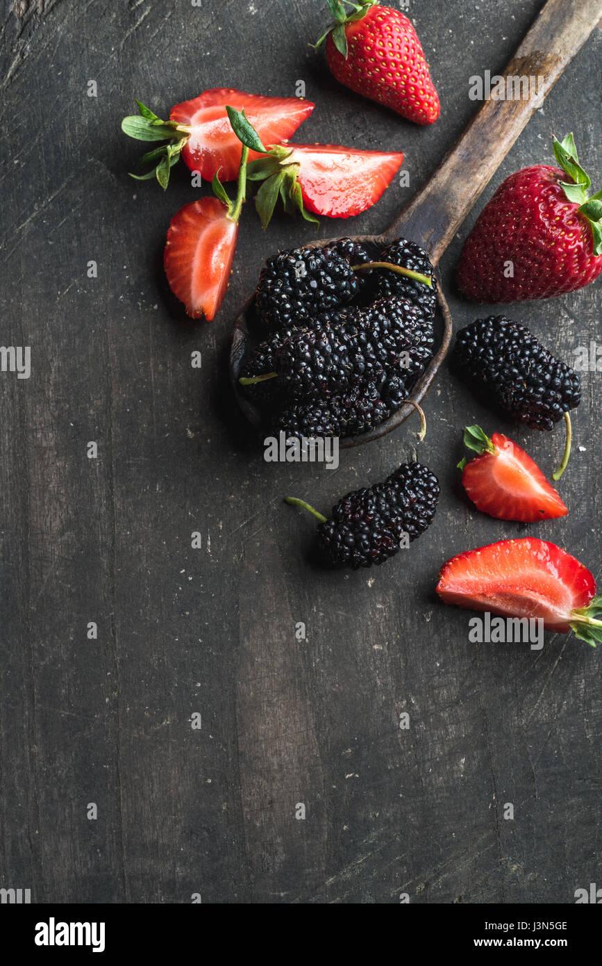 Beeren auf dunklem Holz. Frische Erdbeeren und Maulbeeren in rustikalen Kochlöffel Stockbild