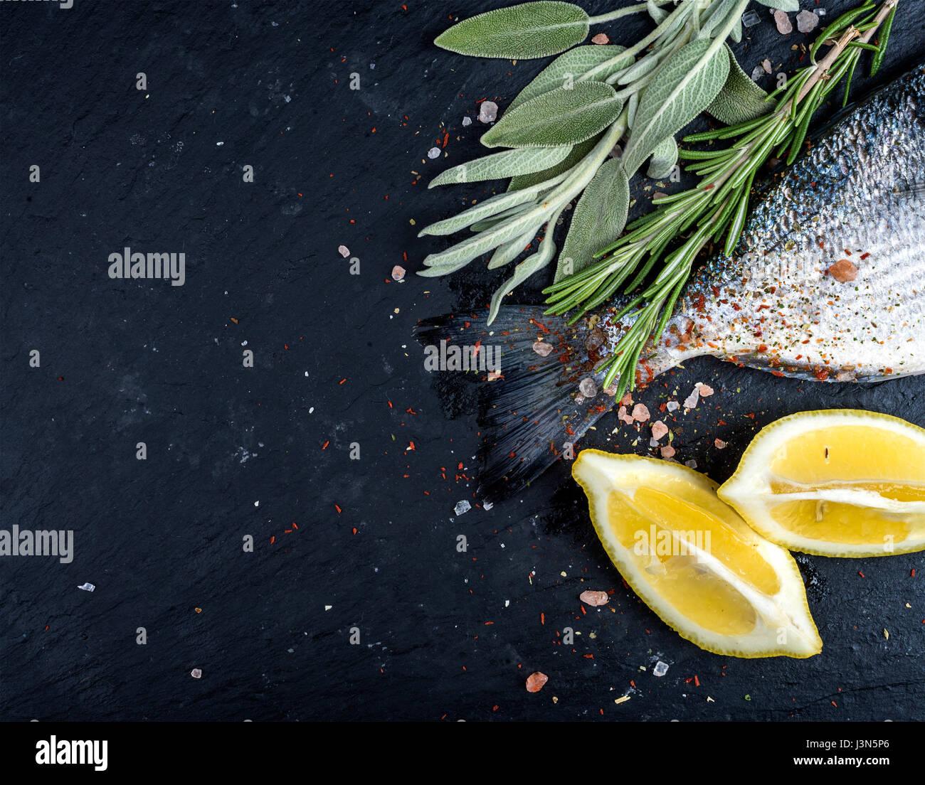 Heck des frischen rohen Dorado oder Dorade Fisch auf schwarzem Schiefer Steinplatte mit Gewürzen, Kräutern, Stockbild
