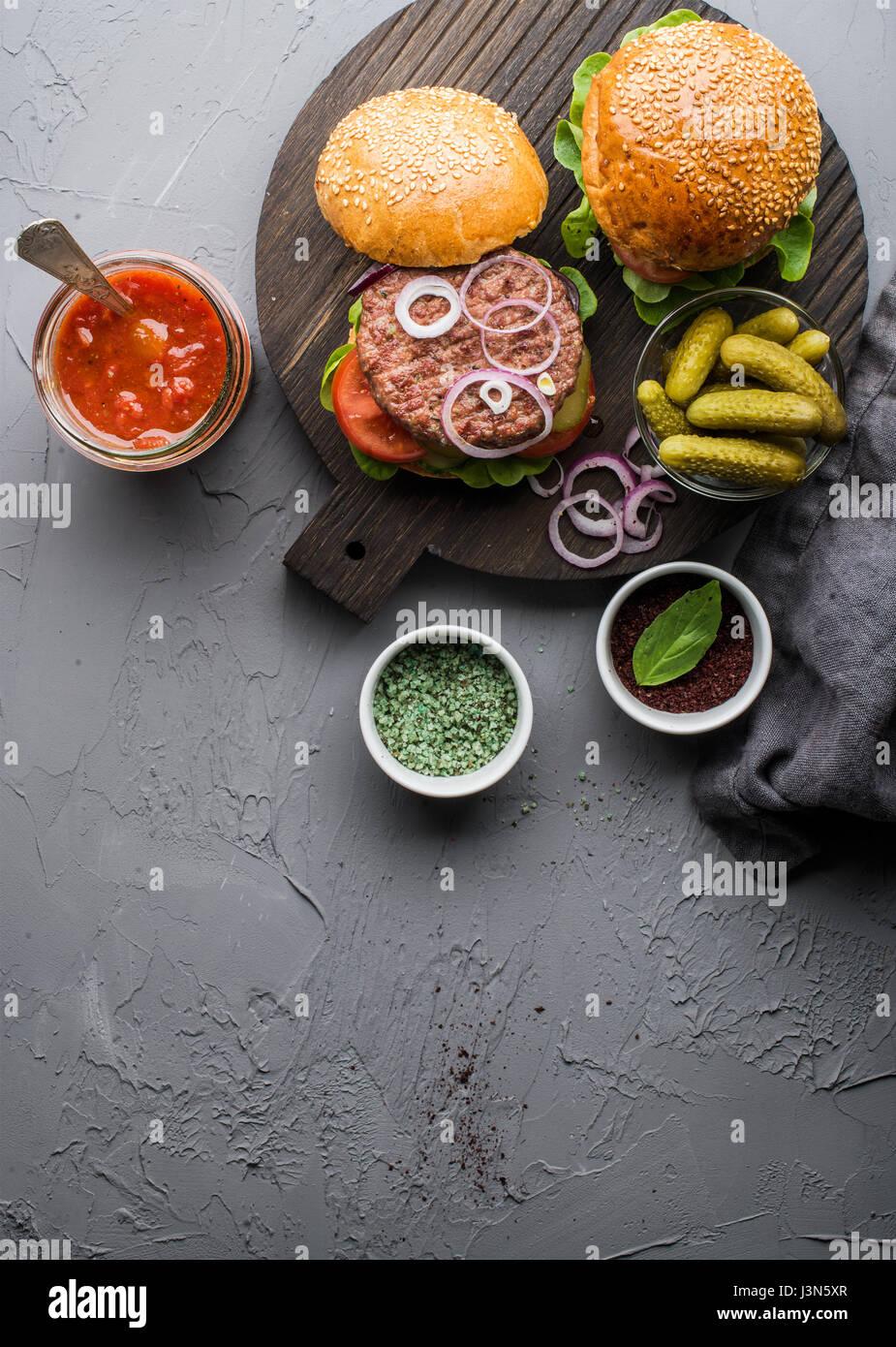 Frische hausgemachte Burger auf dunklen Portion Brett mit würziger Tomatensauce, grüne Salz, Pfeffer, Stockbild