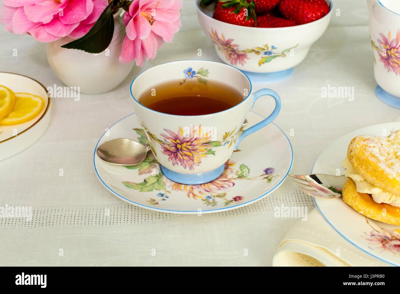 Tasse Tee in einem Vintage Porzellan Teetasse mit frischer Sahne Kuchen serviert. Stockbild