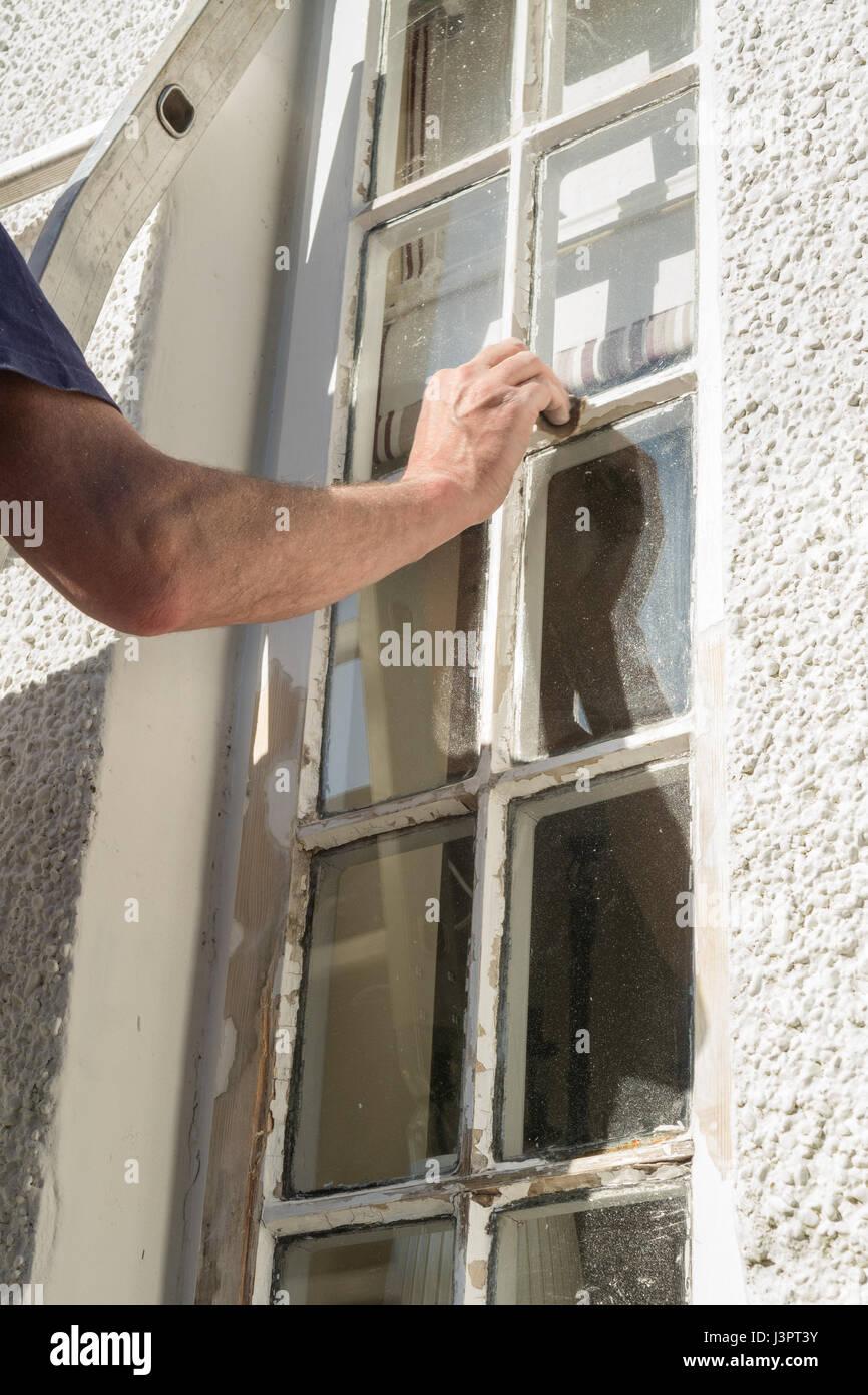 Nach Hause DIY - Mann Schleifen außen Holzfenster in Vorbereitung zum Lackieren Stockbild