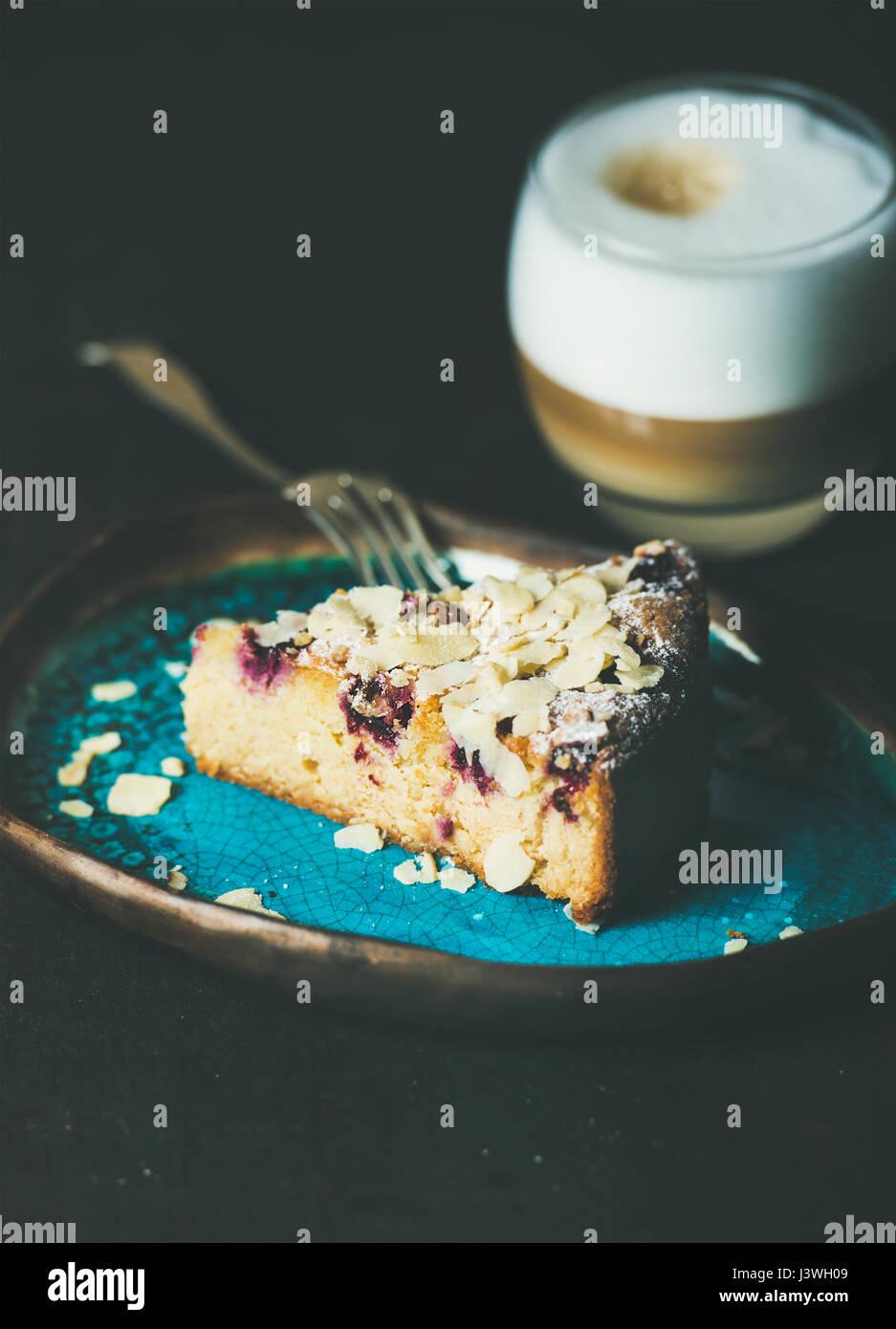 Stück Kuchen und ein Glas Latte auf dunklem Hintergrund Stockbild