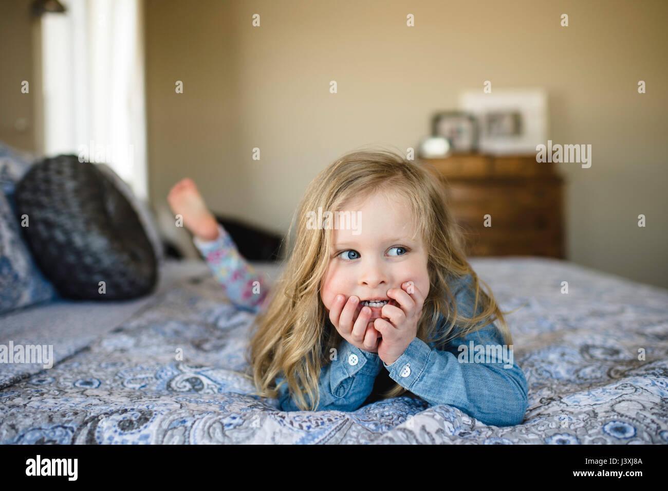 Mädchen auf Bett Blick seitlich liegend Stockbild