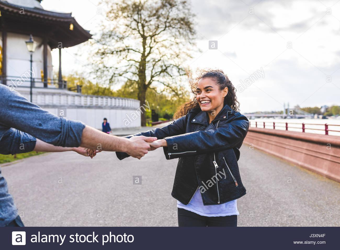 Junge Frau und Freund tanzen und halten sich an den Händen in Battersea Park Stockbild